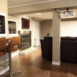 A DSLR photo of a Modern living room located in the basement of a bungalow with a wooden floor, a bar, mimi fridge and fournitures. A beautiful stainless fireplace close to the leather studio couch and a home cinema system with a projector.