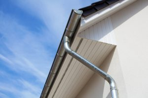 Architectural close-up of a metal rain gutter with downspout